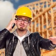 Young Construction Worker on Cell Phone In Front of House — Stock Photo