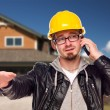 Contractor Wearing Hard Hat on Phone In Front of House — Stock Photo