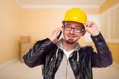Młodzi wykonawcy twardym kapeluszu na telefon komórkowy w domu — Zdjęcie stockowe