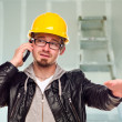 Постер, плакат: Contractor in Hard Hat on Cell Phone In Unfinished House
