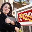 Female Hispanic Real Estate Agent, Vendido Se Vende Sign and Hou - Stock Photo