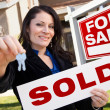 Stock Photo: Hispanic Woman Holding Sold Real Estate Sign and Keys in Front H