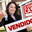 Stock Photo: Hispanic Woman Holding Vendido Sign in Front of Se Vende Casa Si