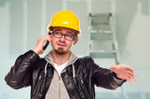 Contractor in Hard Hat on Cell Phone In Unfinished House — Stock Photo