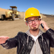 Royalty-Free Stock Photo: Young Cunstruction Worker on Cell Phone in Dirt Field with Tract