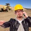 Young Cunstruction Worker on Cell Phone in Dirt Field with Tract - Stock Photo