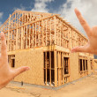 Stock Photo: Female Hands Framing Home Frame on Construction Site