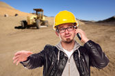 Young Cunstruction Worker on Cell Phone in Dirt Field with Tract — Stock Photo