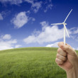 Royalty-Free Stock Photo: Male Fist Holding Wind Turbine Outside with Grass Field