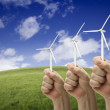 Male Fists Holding Three Wind Turbines Outside - Stock Photo