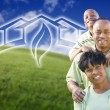 Stock Photo: Happy African American Family and Green House Graphic in Field