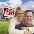 Happy Couple Hugging in Front of Real Estate Sign and House - Stock Photo