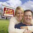 Happy Couple Hugging in Front of Sold Sign and House — Stock fotografie