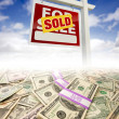 Stacks of Money Fading Off and Sold For Sale Real Estate Sign - Stock Photo
