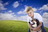 Chico guapo joven jugando con su perro en la hierba — Foto de Stock
