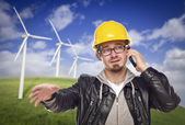 Hard Hat Wearing Engineer on Phone with Turbines Behind — Stock Photo
