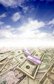 Stacks of Money, Sunburst and Blue Sky — Stock Photo