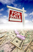 Stacks of Money Fading Off and For Sale Real Estate Sign — Stock Photo