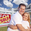 Couple Hugging in Front of Sold Sign and House - Stock Photo