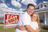 Couple Hugging in Front of Sold Sign and House — Stock Photo