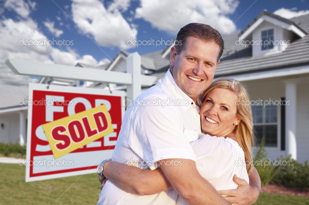 Happy Couple Hugging in Front of Sold Real Estate Sign and House. — Stock Photo #5292834