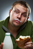 Portrait of funny man with bread and bottle. Yogurt traces on hi — Stock Photo