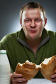 Hungry man with mouth full of bread — Stock Photo
