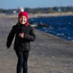 Outdoor portrait of running cheerful little girl — Stock Photo