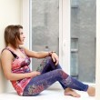 Portrait of attractive young woman sitting on a windowsil — Stock Photo