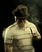 Dark fine art portrait of a smoking man in hat. With tobacco pip — Stock Photo