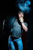 Young muscular man with tire smoking — Stock Photo