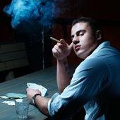 Dark fine art portrait of smoking young gambler — Stock Photo