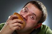 Homem corpulento com fome comendo pão — Foto Stock