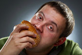 Hungry corpulent man eating white bread — Stock Photo