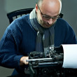 Old fashioned bald writer in glasses writing book on a vintage typewriter — Stockfoto