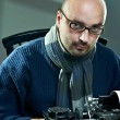 Old fashioned bald writer in glasses writing book on a vintage typewriter — Stock Photo #4476850