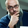 Old fashioned bald writer in glasses writing book on a vintage typewriter — Stockfoto #4476856