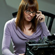 Beautiful young woman in glasses at a typewriter — Foto Stock