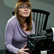 Beautiful young woman in glasses at a typewriter — Stock Photo #4476861
