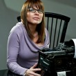 Stock Photo: Beautiful young woman in glasses at a typewriter