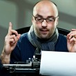 Old fashioned bald writer in glasses writing book on a vintage typewriter — 图库照片