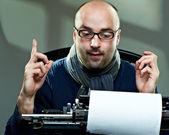 Gamla gammaldags skallig författare i glas skriver bok på en vintage skrivmaskin — Stockfoto