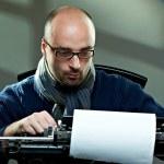 viejo escritor Calvo moda en gafas escribe libro sobre una máquina de escribir vintage — Foto de Stock