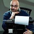Old fashioned bald writer in glasses writing book on a vintage typewriter — Stock Photo #4515280