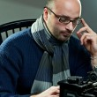 Old fashioned bald writer in glasses writing book on a vintage typewriter — Foto Stock