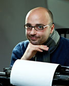 Old fashioned bald writer in glasses writing book on a vintage typewriter — Stock Photo