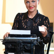Young pretty woman sitting at a typewriter — Stock Photo