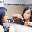 Women near mirror brushing teeth — Stock Photo