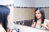Women near mirror brushing teeth — Stock Photo
