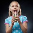 Little girl drinking juice, studio shot — Stock Photo
